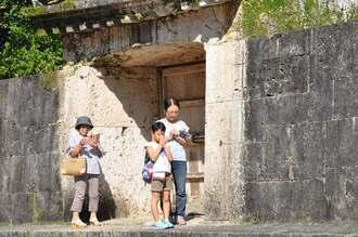 再建を願い、手を合わせる観光客ら=2日、那覇市・首里城公園