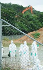 豚コレラ感染があったとみられる養豚場近くで、作業準備をする関係者=12日午後、沖縄市