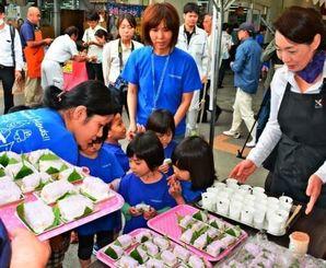 セレモニーでハンダマの押しずしを試食する子どもたち=8日、糸満市・ファーマーズマーケットいとまん