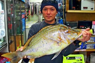 恩納村の海岸で55・5センチ、2・5キロのタマンを釣った新垣孝太さん=22日