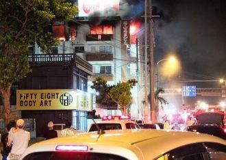 激しく燃えさかる火災現場を心配そうに見詰める近隣住民ら=1日午後7時ごろ、宜野湾市伊佐
