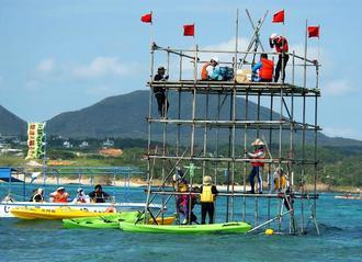ボーリング調査用の資材の一部が運びこまれ、反対派のメンバーがやぐらにのぼり抗議をしている=2004年11月22日、沖縄県名護市・辺野古漁港付近