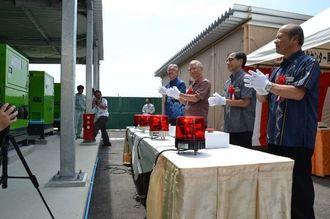 浦崎副知事(右から3人目)らがスイッチを押し、発電機が動くと拍手が起きた=15日、うるま市州崎・具志川浄化センター