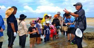 見つけた生き物の特徴を説明する浪岡光雄さん(右端)=7日、キャンプ・キンザー沖のカーミージー周辺