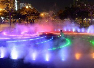 霧の噴水がイルミネーションに照らされ、幻想的な雰囲気を演出する=1日、那覇市おもろまち
