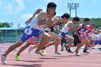 陸上競技で、いきよいよくスタートする選手たち=28日、沖縄市陸上競技場