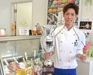 国際コンクールで準グランプリに輝いたジェラートとトロフィーを手に喜ぶ米盛勝也さん=2日、宜野湾市嘉数・「la Vous」