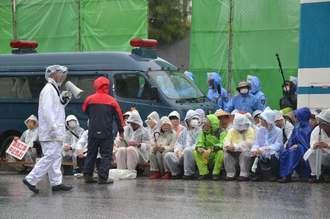雷雨の中、かっぱを着て新基地建設に抗議する人々=13日午前8時50分ごろ、名護市辺野古の米軍キャンプ・シュワブ前