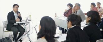 みとりについての新屋洋平医師(左)の講演に聞き入る参加者=7日、なは市民協働プラザ