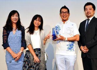 トロフィーを掲げる担当の依岡氏(左から3人目)