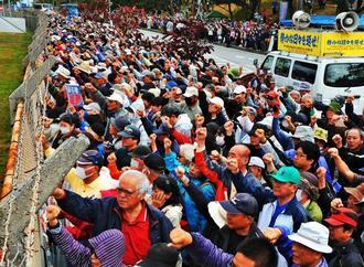 米軍キャンプ・シュワブに向かい抗議の声を上げる集会参加者=25日午後、名護市辺野古(伊禮健撮影)