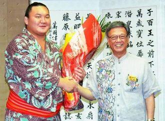 表敬で訪れた横綱白鵬(左)と笑顔で握手する翁長雄志知事=25日、沖縄県庁