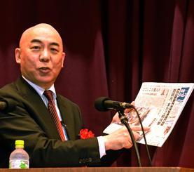 本紙を示しながら講演する百田尚樹氏=10月27日、名護市・数久田体育館
