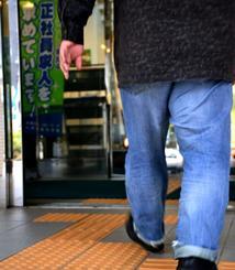 ハローワークに向かう真栄城さん。玄関には「正社員求人を求めています」ののぼりが立っていた=那覇市内