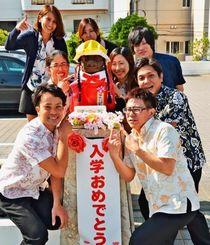 4月 シーサー小学校のサーちゃん(中央)と、着せ替え担当の従業員たち=15日、浦添市伊祖のイースペース