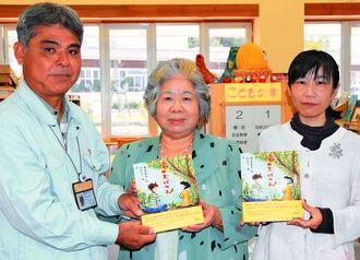 絵本を出版した平良正子さん(中央)と作画を担当した矢野綿子さん(右)、寄贈を受けた南風原町立図書館の神里智館長=日、南風原町