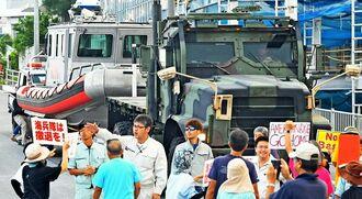 米軍車両の入港を阻止しようとする市民と沖縄防衛局関係者ら=17日午前7時すぎ、本部町・本部港前(国吉聡志撮影)