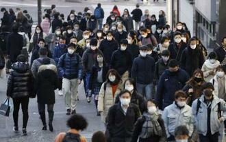 東京・新宿を歩くマスク姿の人たち=21日午後