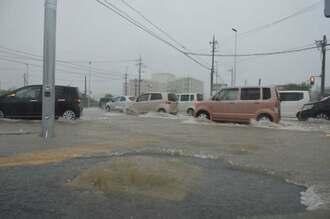 南風原町新川南部医療センター付近でも道路が冠水。深いところで膝下まで雨水が溜まった=26日午前8時40分ごろ