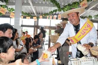 マンゴー共和国の建国イベントで共和国の教授にふんした生産農家(右)からお菓子をもらう市民ら=18日、宮古島市の島の駅「みやこ」