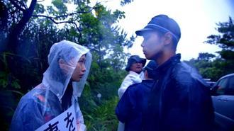 「標的の島 風かたか」のワンシーン。雨が降りしきる中、機動隊員と女性の視線が交錯する