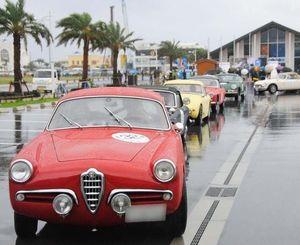 雨の中、ラリーに出発するクラシックカー=23日、北谷町美浜のうみんちゅワーフ