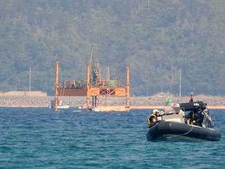 掘削棒を下ろすスパッド台船=3日午前10時半ごろ、名護市の大浦湾