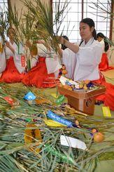 笹に短冊やひょうたんを結び付け、福笹を作る巫女たち=26日、那覇市奥武山・護国神社