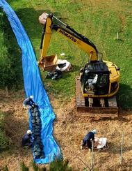 旧ジュマールゴルフガーデン内に土のうを設置する作業員=1日午後4時40分、石垣市平得大俣(小型無人機で撮影)