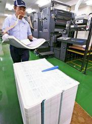 印刷されたマイナンバーの通知カードを台車に積み上げる作業員=2日、東京都の国立印刷局東京工場