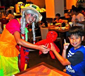 子どもたちの笑顔を楽しみに、バルーンアートを作っている「島ピエロのゆずちゃん」こと明石光佐さん(左)=21日、宮古島市上野宮国