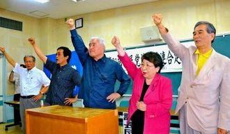 新役員と運動方針を決定しガンバロー三唱する社民党県連の新里米吉委員長(中央)ら=沖縄市農民研修センター