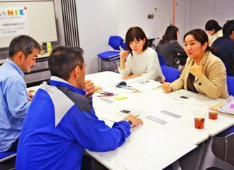 グループワークで各校の事例を報告する参加者=24日、那覇市・沖縄タイムス社