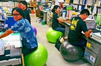 バランスボールに座って業務に励む北中城村職員=村役場