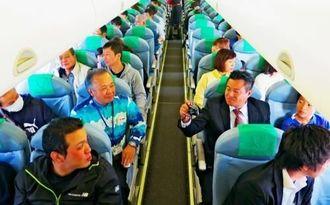 伊良部大橋や宮古島周辺の島々を巡る遊覧飛行を楽しむ参加者=FDA機内