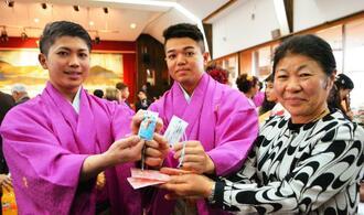 新成人にお守りを贈呈する仲田スミ子部長(右)=宜野座村立中央公民館