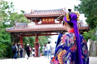 観光客が減り、守礼門前で記念撮影業をする女性の仕事も減っているという=那覇市首里(下地広也撮影)