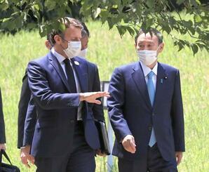 会談を終え、昼食会場に向かう菅首相(右)とフランスのマクロン大統領=24日午後、東京・元赤坂の迎賓館(代表撮影)