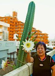 未明に開いた白い花と、金城ミエさん。「台風からも守ってくれ、お父さんが旧盆前に咲かせてくれたみたい」と喜んでいる=3日午前6時すぎ、那覇市宇栄原・金城さん宅屋上