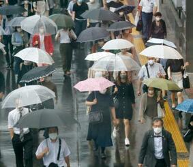 マスク姿で東京・新宿を歩く人たち=13日午後5時45分