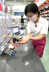 消毒ロボットを利用する佐和田優里さん=14日、うるま市・沖縄アミークスインターナショナル小学校