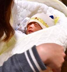 母・李さんに抱っこされ、台湾に帰国する赤ちゃん=24日夜8時10分すぎ、那覇空港国際線
