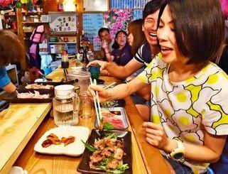 ヤギ料理をおいしそうに食べる観光客の女性=10日午後、那覇市牧志の「さかえ」