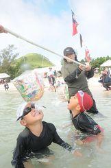 渡名喜小中学校伝統の水上運動会で障害物競走を楽しむ子どもたち=25日、あがり浜