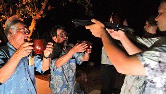 「ヤッカ、ヤッカ」の掛け声が辺りに響く中、ミス(神酒)を飲む地域住民ら=21日午後11時半ごろ、多良間村塩川