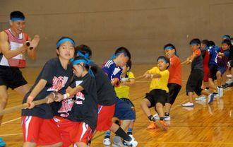 力を合わせて綱を引くレイザーラモンHGさん(左)チームの子どもたち=宜野湾市立体育館