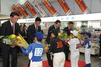 歓迎式で少年野球チームから花束を贈呈される梨田昌孝監督(右から2人目)ら=久米島空港