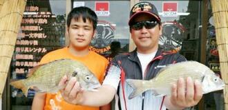 中部海岸で41センチ、1.01キロのミナミクロダイを釣った城間護さん(右)と悠太さん=1日