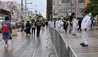 国際通りのてんぶす那覇前を警戒する警察官ら。新成人らによる大きな混乱はなかった=7日午後5時20分ごろ、那覇市牧志