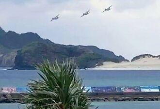 座間味村上空を編隊飛行する機体=6日午後、同村(島袋裕二さん撮影)